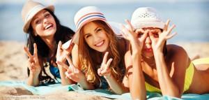 Drei Freundinnen liegen am Strand und genießen ihren Urlaub