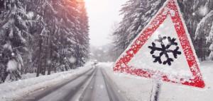Verschneite Straße mit rotem dreieckigem Warnschild mit einer Schneeflocke