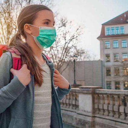 Schülerin mit Rucksack vor Schule