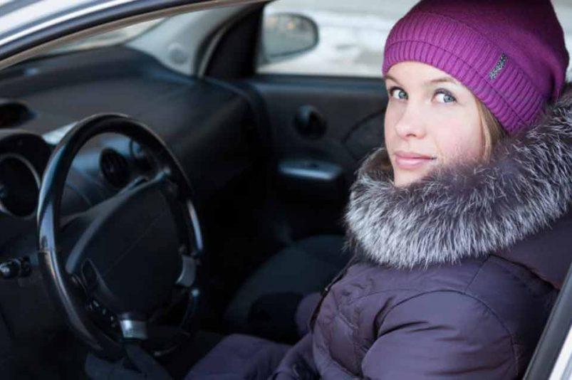 Frau mit Winterkleidung am Steuer