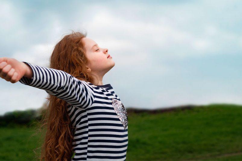 Ein kleines Mädchen atmet frei auf einer Wiese