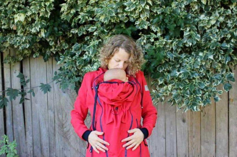 Mutter trägt ihr Baby in einer roten Tragejacke