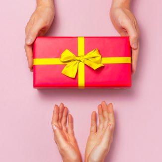 ein rotes Geschenk mit gelber Schleife wird überreicht