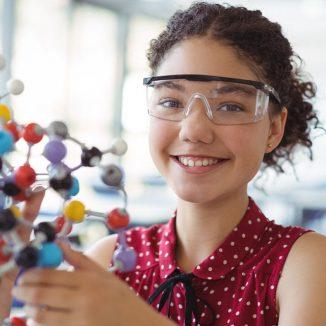 Ein Mädchen hält ein Molekülmodell in ihren Händen